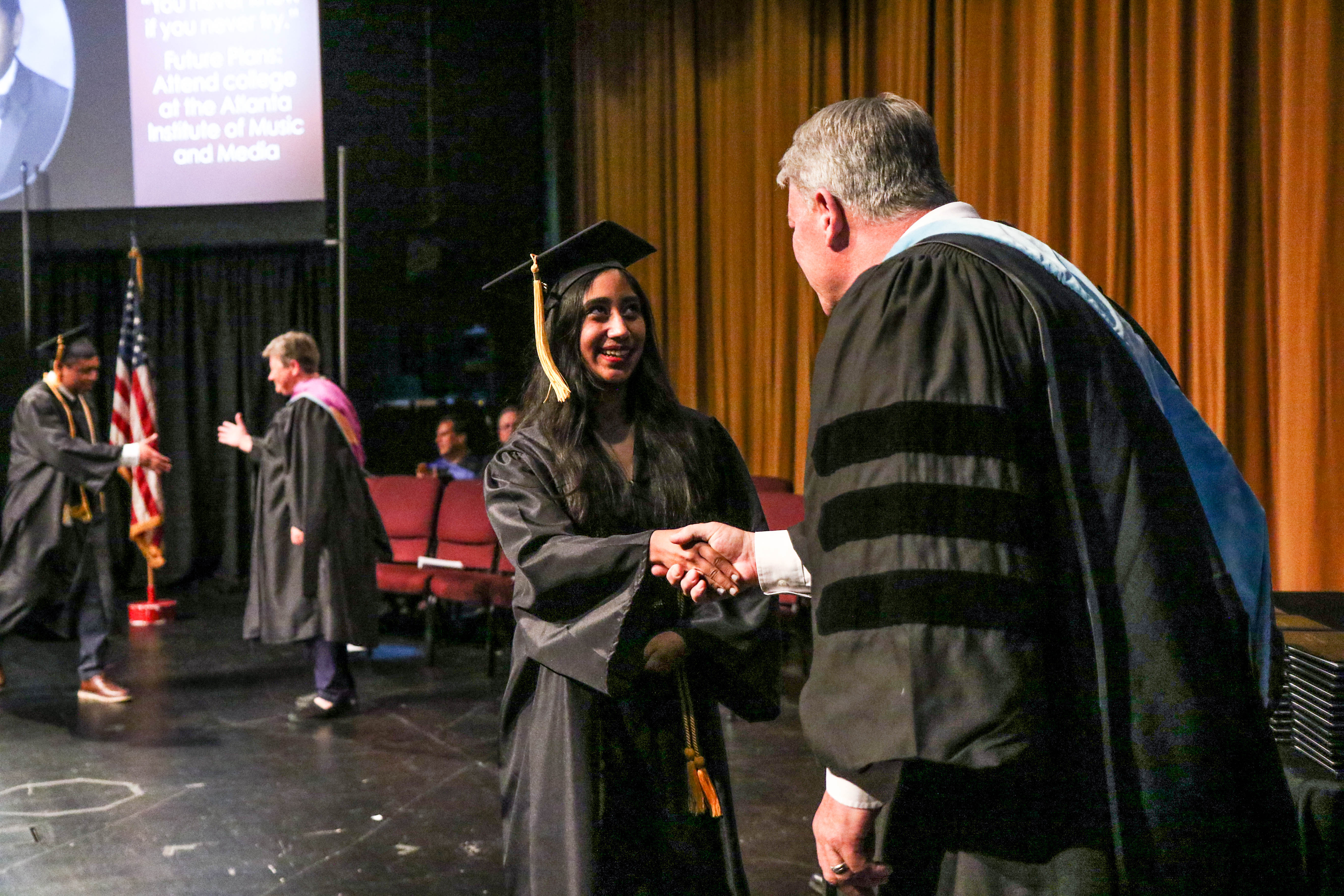 Dr. Scott shaking hands with graduate