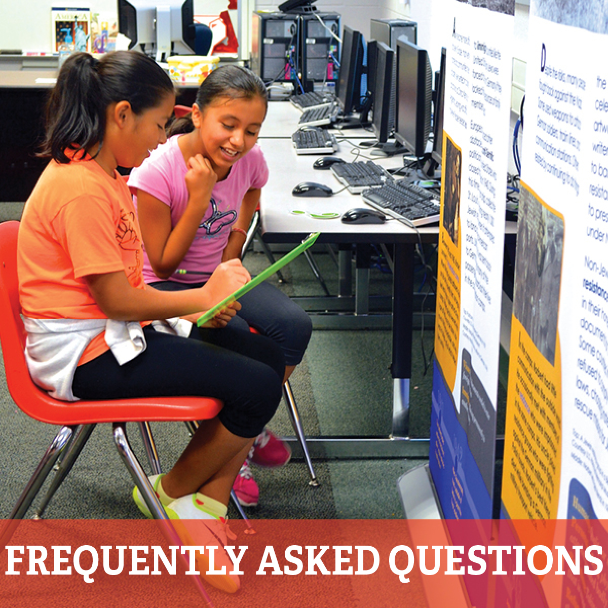 "Two female students looking at poster with text that reads, ""Frequently asked questions"""