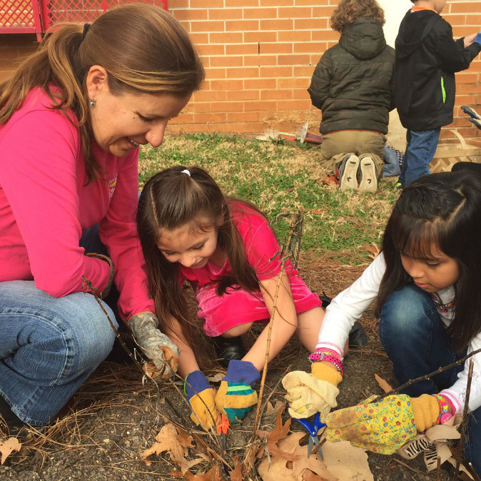 Teacher planting tree with two female students