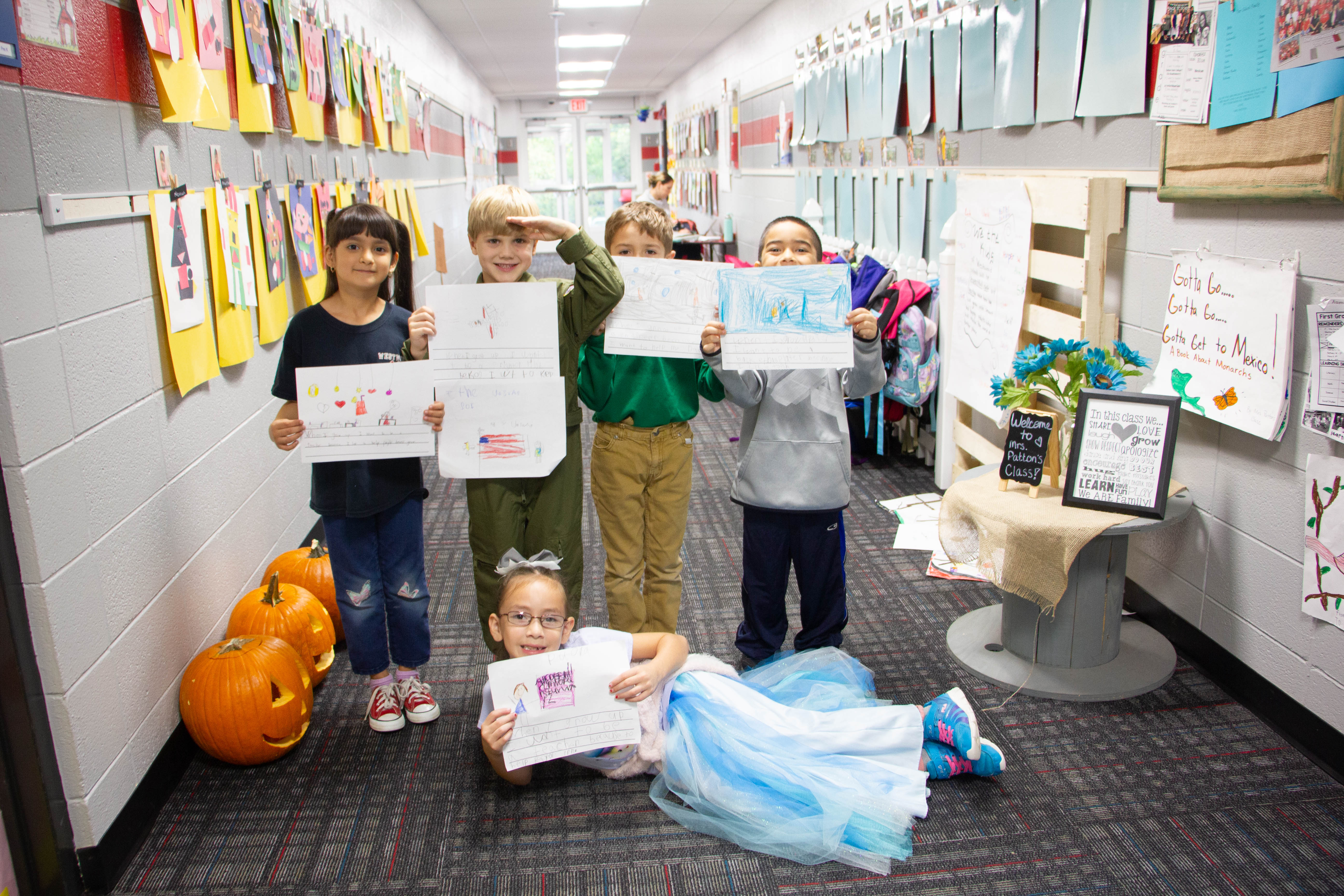 Students in costumes holding signs describing what they want to be when they grow up
